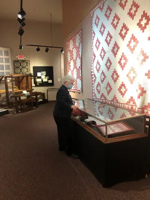 Carol Dunn, Executive Director, Wayne County Historical Society, inspects part of the new exhibit, Threads of Our Lives, at the Main Museum. The exhibit, and another new exhibit, History of Wayne County's Independent Pharmacies, will be open to the open to the public, Saturday May 22. The Open House is from 11 a.m. to 4 p.m. and features free admission that day.